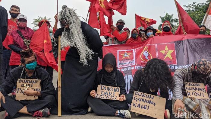 Massa aksi demo Omnibus Law melakukan aksi teatrikal di kawasan Patung Kuda, Jakarta. Mereka berkotum ala dukun dari berbagai daerah. Penasaran?