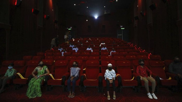 People watch an Indian Bollywood movie as cinemas reopen with a special screening for COVID- 19 warriors and their families at the PVR movie theater in New Delhi, India, Thursday, Oct. 15, 2020. Seven months after screens went dark, cinemas reopened Thursday in much of India with mostly old titles on the marquee — a sign of the country's efforts to return to normal as the pace of coronavirus infections slows but also of the roadblocks that remain. (AP Photo/Manish Swarup)