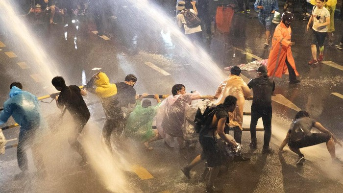 Police use water canons to try and disperse demonstrators from their protest venue in Bangkok, Thailand, Friday, Oct. 16, 2020. Thailand prime minister has rejected calls for his resignation as his government steps up efforts to stop student-led protesters from rallying in the capital for a second day in defiance of a strict state of emergency. (AP Photo/Sakchai Lalit)