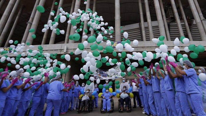 Medical workers embrace while they celebrate as the last three patients are released from a field hospital at the National Stadium Mane Garrincha, after recuperating from COVID-19, in Brasilia, Brazil, Thursday, Oct. 15, 2020. (AP Photo/Eraldo Peres)