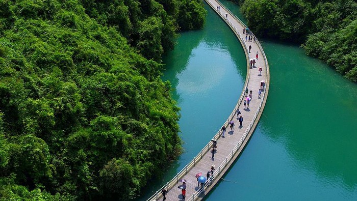 Ini adalah jalan terapung yang ada di China. Pemandangan sekelilingnya tampak sangat memanjakan mata. Begini penampakannya.