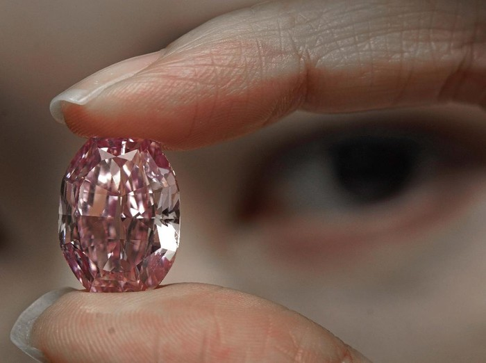 An ultra-rare 14.83-carat diamond that is one of the largest internally flawless fancy vivid purple-pink gem ever graded by the Gemological Institute of America is displayed by a model at a Sothebys auction room in Hong Kong Monday, Oct. 12, 2020. The diamond will sale in Geneva on Nov. 11. (AP Photo/Vincent Yu)