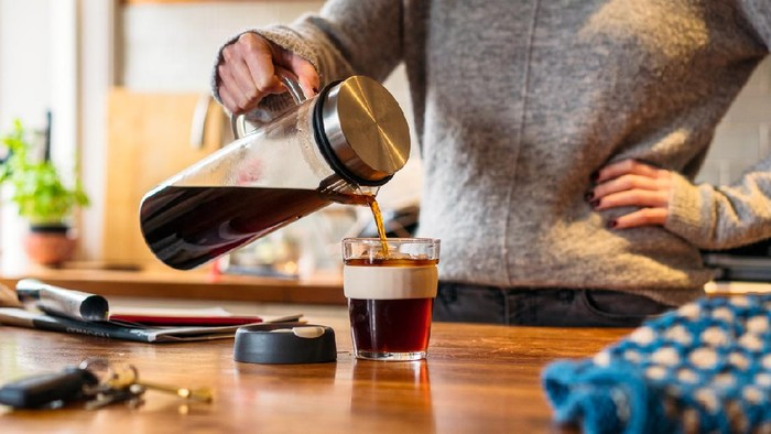 A woman pouring cold-brew coffee into a re-usable mug in the kitchen.