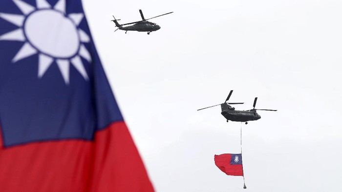 Helicopters fly over President Office with Taiwan National flag during the National Day celebrations in Taipei, Taiwan, Saturday, Oct. 10, 2020. Taiwanese President Tsai Ing-wen said Saturday she has hopes for less tensions with China and in the region if Beijing will listen to Taipei's concerns, alter its approach and restart dialogue with the self-ruled island democracy. (AP Photo/Chiang Ying-ying)