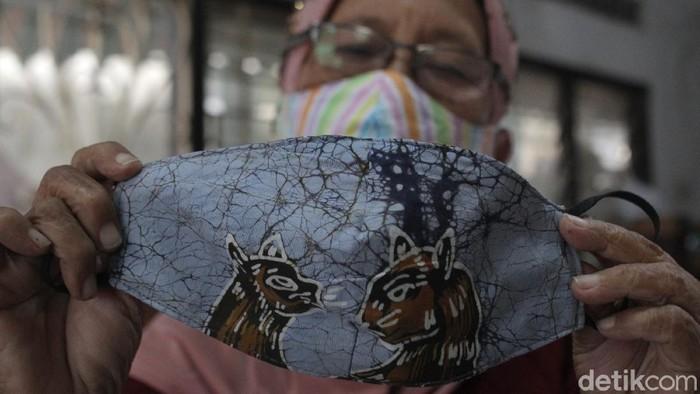 Pekerja menyelesaikan pembuatan masker kain di industri rumahan Batik Seno, Yogyakarta, Senin (19/10/2020).