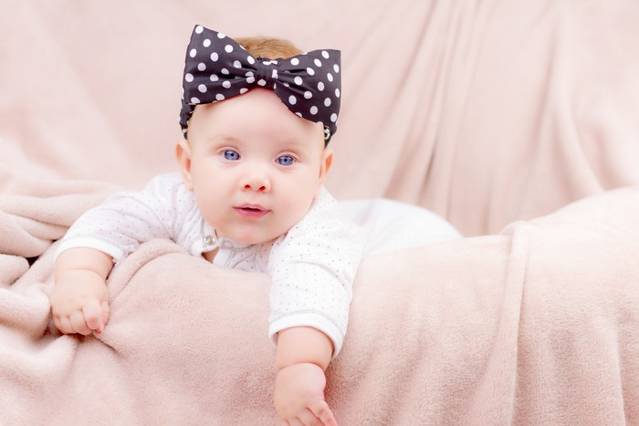 Portrait of a beautiful baby girl with the black band on her head  lying on the sofa