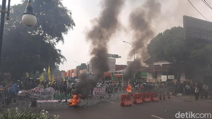 Sejumlah mahasiswa melakukan aksi memperingati satu tahun pemerintahan Jokowi-Maruf Amin di sekitar istana bogor. Mereka membakar ban dan membawa keranda menuju Istana Bogor.