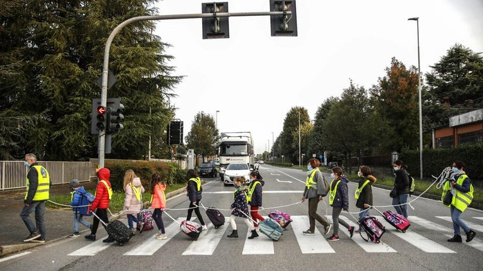 Children, escorted by volunteers, walk to school holding on to a rope to help maintain social distancing and curb the spread of COVID-19, in Bellusco, northern Italy, Tuesday, Oct. 20, 2020. (AP Photo/Luca Bruno)
