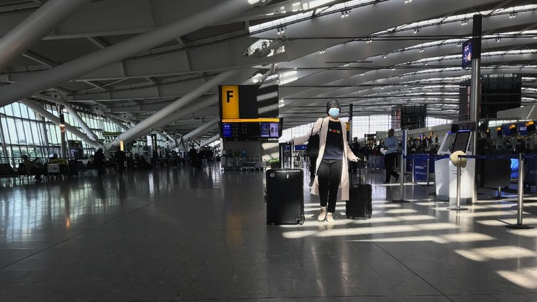 FILE - In this Tuesday, March 24, 2020 file photo, a woman wears a mask as she walks through a quieter than usual Heathrow Airport Terminal 5, in London. Air traffic is down 92% this year as travelers worry about catching COVID-19 and government travel bans and quarantine rules make planning difficult. One thing airlines believe could help is to have rapid virus tests of all passengers before departure. (AP Photo/Kirsty Wigglesworth, File)