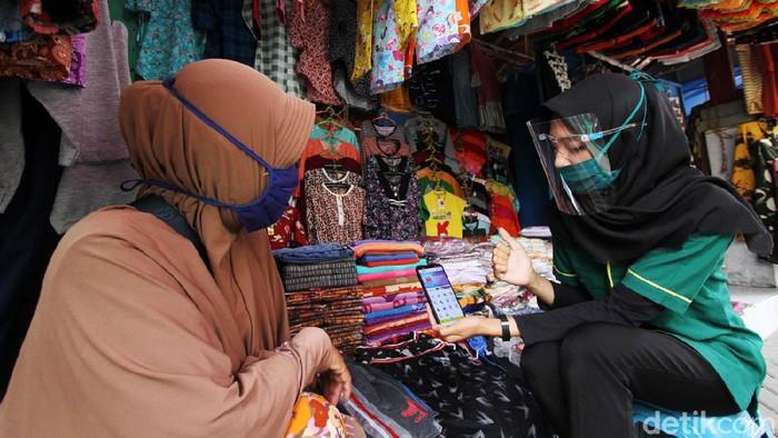 Pegawai bank Mandiri Syariah memperkenalkan penggunaan mobile banking kepada pedagang di pasar Gawok, Sukoharjo, Jawa Tengah, Senin (19/10). Mandiri Syariah Mobile (MSM) salah satu program untuk mendukung pemerintah dalam mengkampanyekan transaksi secara nontunai sekaligus mempermudah melakukan transaksi pembayaran ditengah pandemi COVID-19 seperti donasi, berbelanja dan zakat di masjid tanpa harus keluar rumah.