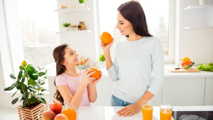 Beautiful lovely nice charming cheerful mom and her small little daughter in casual, holding, showing each other grapefruits, healthy natural orange fresh juice on table in light kitchen