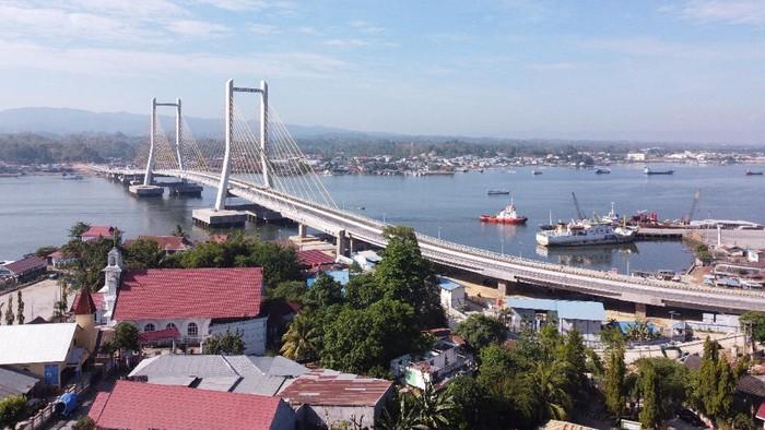 Pengendara motor melintas di bawah Jembatan Teluk Kendari yang telah tuntas pembangunannya di Kendari, Sulawesi Tenggara, Rabu (21/10/2020). Presiden Joko Widodo rencananya akan meresmikan Jembatan Teluk Kendari sepanjang 1,34 Kilometer pada Kamis (22/10/2020). ANTARA FOTO/Jojon/wsj.