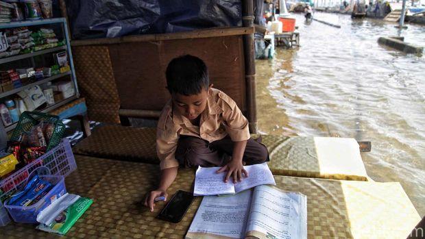 Seorang siswa SD tetap belajar secara daring saat banjir rob menerjang kawasan Pelabuhan Kali Adem, Muara Angke, Jakarta Utara. Begini potretnya.
