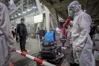 Para petugas bandara terlihat sibuk menyemprotkan disinfektan ke semua barang yang dibawa oleh turis. (AP/Wason Wanichakorn)