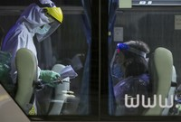 Sebelum keluar dari bandara, petugas kesehatan mengecek turis untuk terakhir kalinya. (AP/Wason Wanichakorn)
