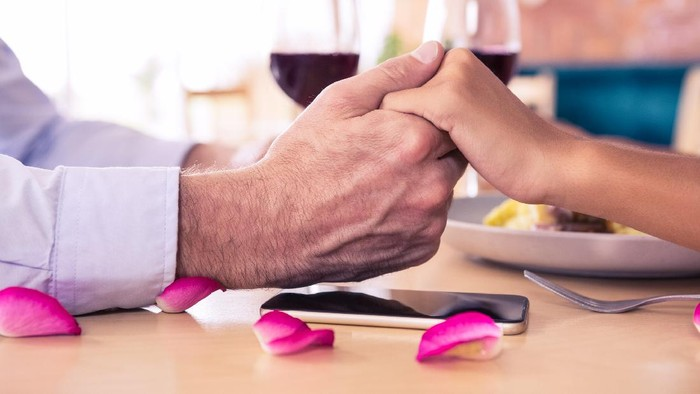 Man holding hands of woman in restaurant