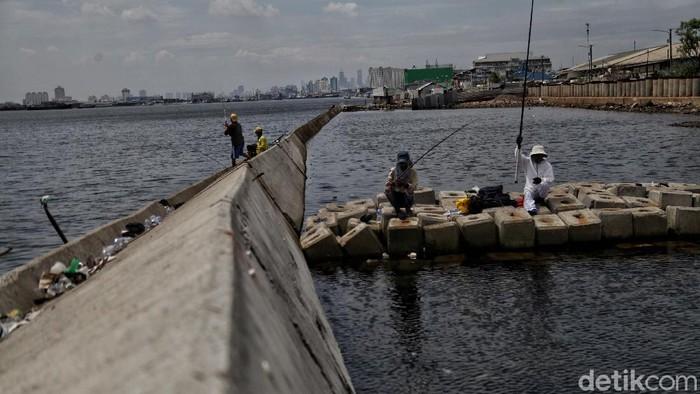 Sejumlah warga memancing di kawasan tanggul laut yang roboh di Pelabuah Nizam Zachman Muara Baru, Jakarta Utara, Kamis (22/10/2020).