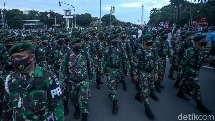 Pasukan TNI bantu menggerakkan massa buruh untuk bergegas membubarkan diri di kawasan Patung Kuda. Aksi buruh tersebut berjalan damai.