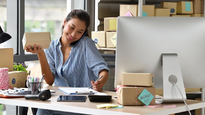 Working women at their store. They wearing casual clothing, accepting new orders online and packing merchandise for customer