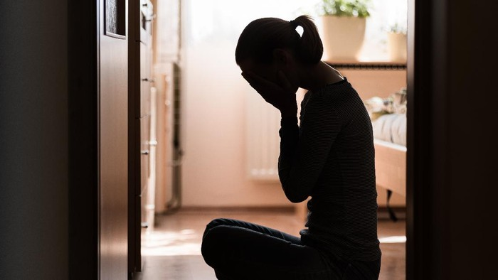 Sad young woman sitting on room floor crying with hand over face