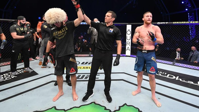 ABU DHABI, UNITED ARAB EMIRATES - OCTOBER 25: In this handout image provided by UFC, (L-R) Khabib Nurmagomedov of Russia celebrates his victory over Justin Gaethje in their lightweight title bout during the UFC 254 event on October 25, 2020 on UFC Fight Island, Abu Dhabi, United Arab Emirates. (Photo by Josh Hedges/Zuffa LLC via Getty Images)