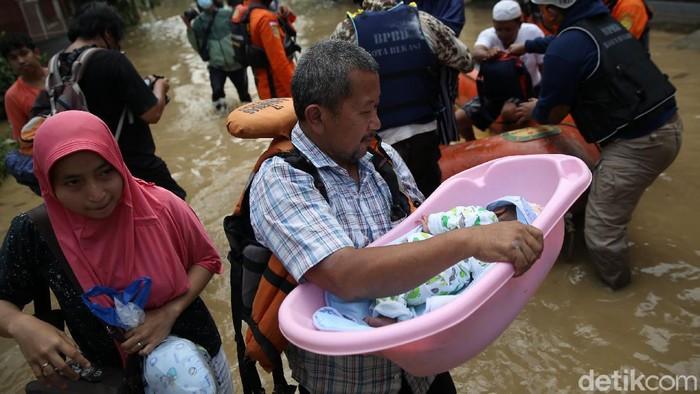 Petugas Basarnas mengevakuasi bayi dan orang tuanya saat banjir di kawasan Jatirasa, Bekasi, Jawa Barat. Berikut foto-fotonya.