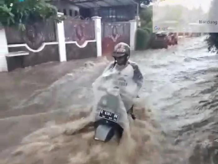 Pengendara motor di Bandung terseret aliran air yang deras.