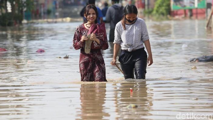 Warga melintasi banjir di Perumahan Pondok Gede Permai, Kota Bekasi, Jawa Barat, Minggu (25/10/2020). Sejumlah wilayah di banjir sejak semalam terendam banjir. Salah satunya banjir berada di Perumahan Pondok Gede Permai pagi ini setinggi 90 cm. Agung Pambudhy/Detikcom.