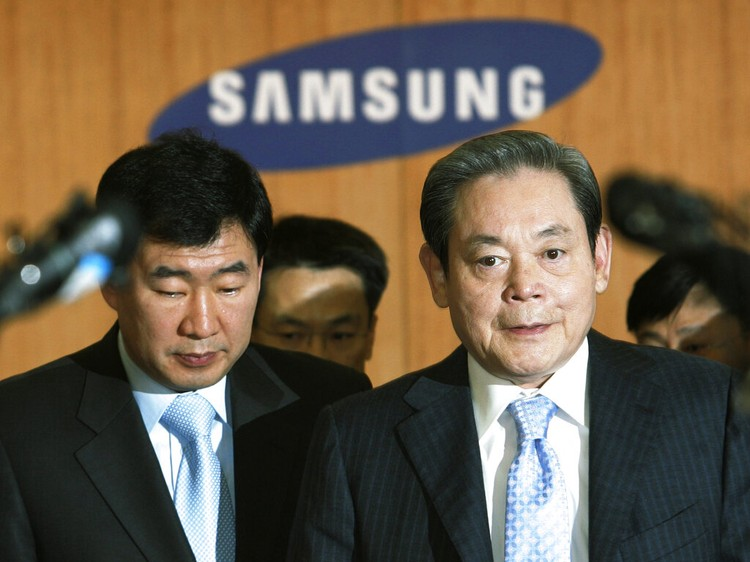 FILE - In this July 6, 2011, file photo, Samsung Chairman Lee Kun-hee, right, greets people from the South Korean delegation in Durban, South Africa, for the 123rd International Olympic Committee (IOC) session that will decide the host city for the 2018 Olympics Winter Games. Lee, the ailing Samsung Electronics chairman who transformed the small television maker into a global giant of consumer electronics, has died, a Samsung statement said Sunday, Oct. 25, 2020. He was 78. (AP Photo/Schalk van Zuydam, File)