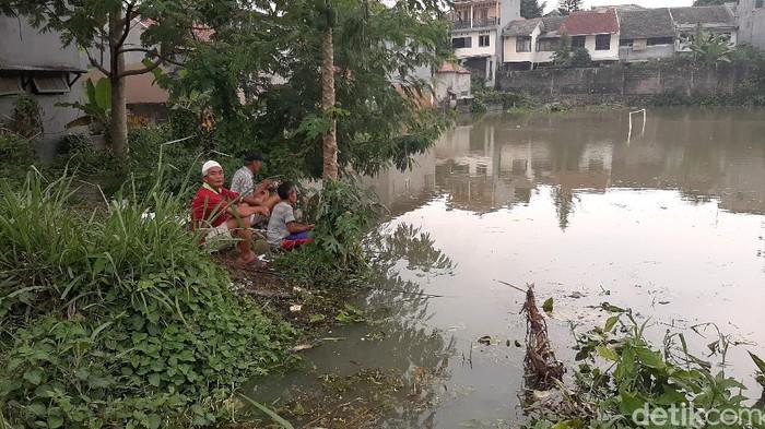 Warga manfaatkan lapang sepak bola yang terendam banjir untuk memancing.