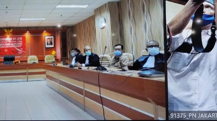 Benny Tjokro dan Heru Hidayat menghadiri sidang secara virtual (foto dari layar di ruang sidang).