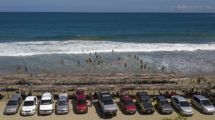 Tourists cars are parked along Los Angeles beach after it recently reopened following a lockdown to contain the spread of COVID-19 in La Guaira, Venezuela, Friday, Oct. 23, 2020. Strict quarantine restrictions forced the closure of beaches across the country in March and reopened this week. (AP Photo/Matias Delacroix)