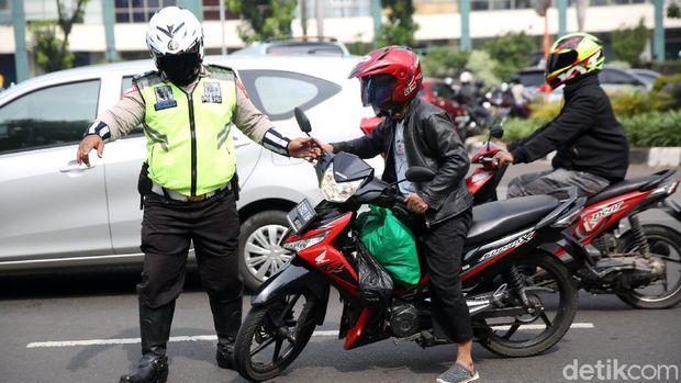 Anggota Polisi Satua Lalu Lintas Polres Jakarta Timur melakukan razia kendaraan bermotor di Jalan DI Panjaitan, Cawang, Jakarta Timur, Senin (26/10/2020). Operasi Zebra 2020 mulai digelar Senin (26/10). Ada lima jenis pelanggaran yang menjadi prioritas sasaran penindakan dalam operasi yang akan berlangsung hingga 8 November mendatang.