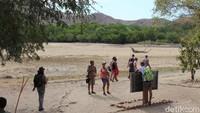 Pengunjung turis mancanegara berpose dengan papan taman nasional Komodo di Pulau Rinca.