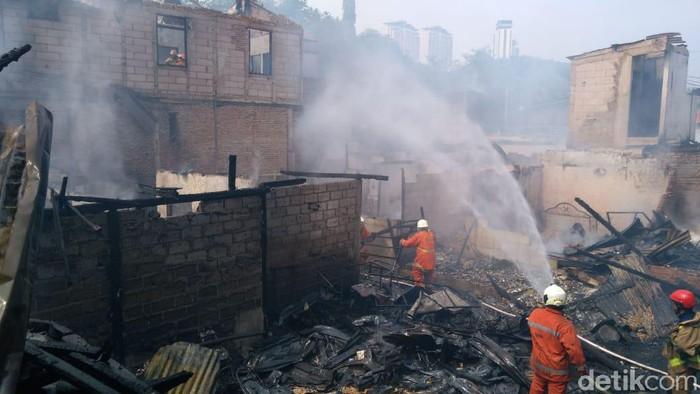 Petugas damkar memadamkan api di permukiman Simprug, Jakarta Selatan.