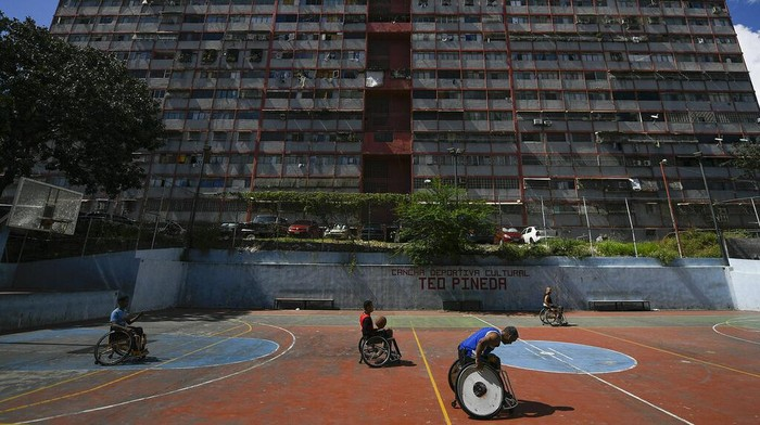 Wheelchair-bound basketball players drive to get to the ball during a game at a public court of the Artigas neighborhood of Caracas, Venezuela, Saturday, Oct. 24, 2020, amid the new coronavirus pandemic. Manuel Mendoza, leader of the Spinal Cord Injury Foundation of Venezuela, organizes wheelchair basketball tournaments in the popular neighborhoods of Caracas. For us it is very complicated to move around in this city. The infrastructure is almost non-existent, in the subway, in the streets. It is not adequate as it should be. We always have transportation problems especially with the subway since we cannot enter with our wheelchairs, says Mendoza.  (AP Photo/Matias Delacroix)
