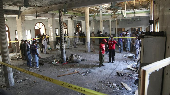 People comfort a cleric who mourns over lost of his students at the site of a bomb explosion in an Islamic seminary, in Peshawar, Pakistan, Tuesday, Oct. 27, 2020. A powerful bomb blast ripped through the Islamic seminary on the outskirts of the northwest Pakistani city of Peshawar on Tuesday morning, killing some students and wounding dozens others, police and a hospital spokesman said. (AP Photo/Muhammad Sajjad)