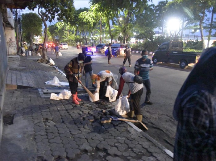 Wali Kota Surabaya Tri Rismaharini membersihkan batu di sepanjang Jalan Pahlawan hingga Kramat Gantung. Ini untuk mencegah aksi lempar batu dalam demo Omnibus Law.