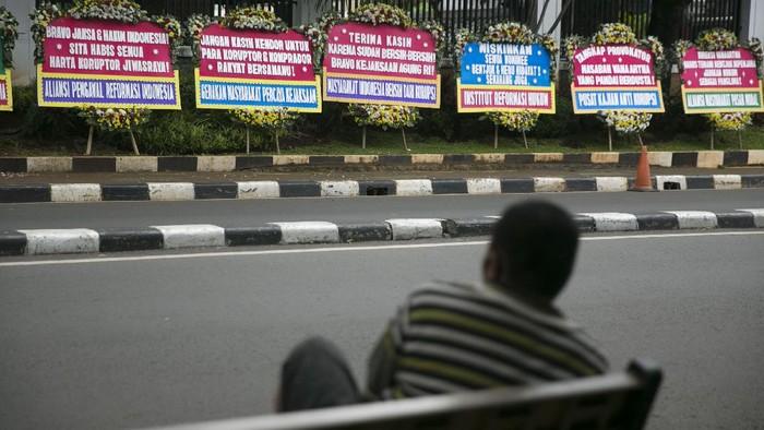 Warga melintas di depan karangan bunga di depan gedung Kejaksaan Agung, Jakarta, Selasa (27/10/2020). Karangan bunga tersebut sebagai bentuk dukungan dan dorongan bagi kejagung untuk mengusut tuntas kasus gagal bayar WanaArtha Life. Dan apresiasi atas penyelesaian kasus PT Asuransi Jiwasraya (Persero) .