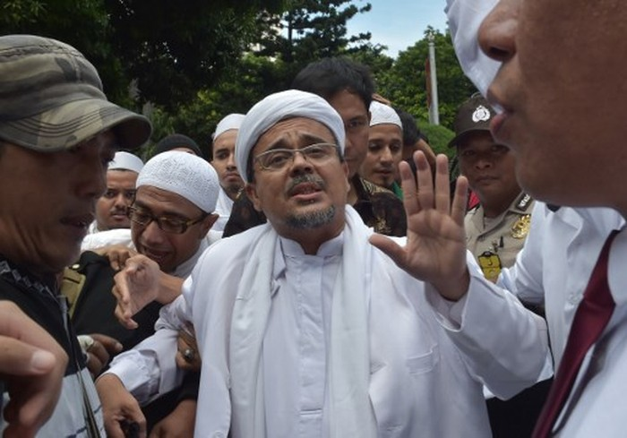 Rizieq Shihab, leader of the Indonesian hardline Muslim group FPI (Front Pembela Islam or Islamic Defender Front), arrives at the police headquarters in Jakarta on January 23, 2017. - Shihab was summoned as a witness by police over allegations he insulted rupiah bank notes by saying they contained communist symbols. (Photo by ADEK BERRY / AFP)