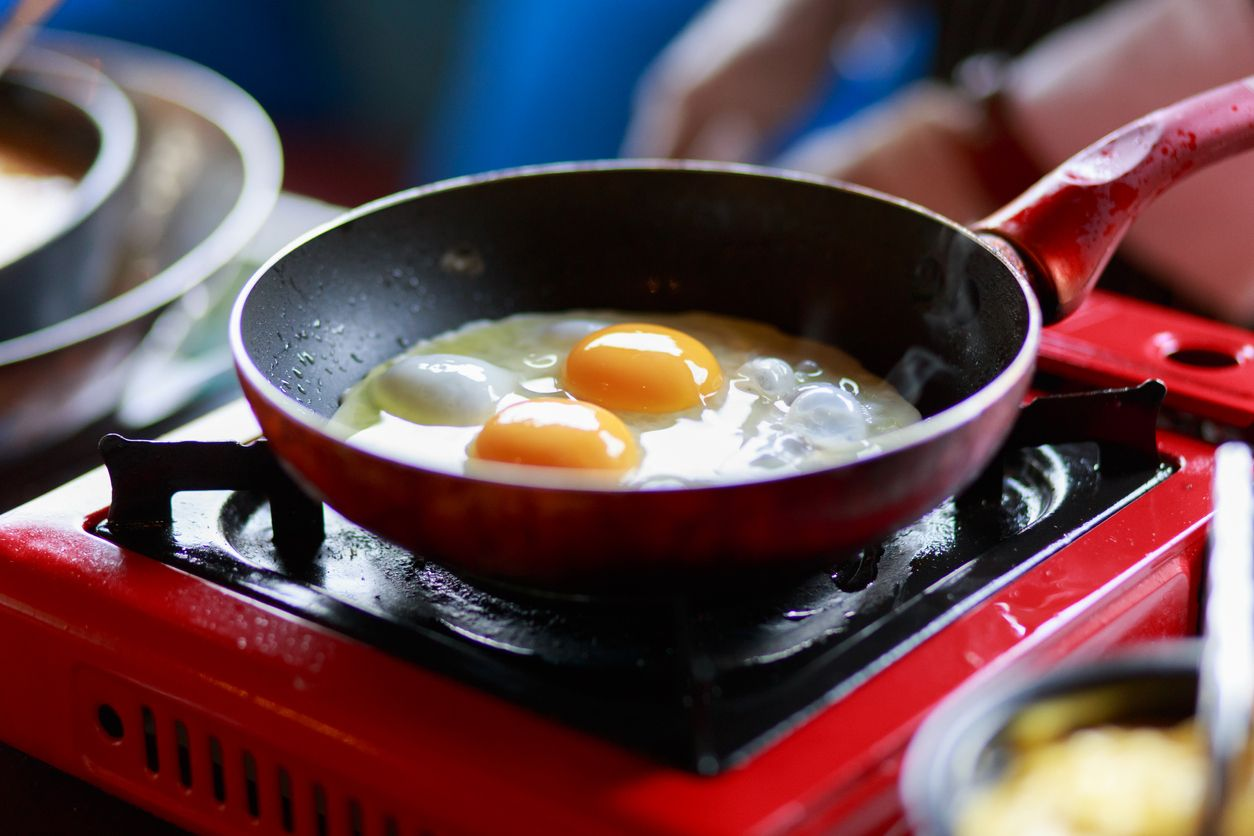 Cooking Eggs Sunny-side-up in a non-stick pan on a gas stove. Frying a batch of eggs for breakfast in a non-stick pan with a gas stove.