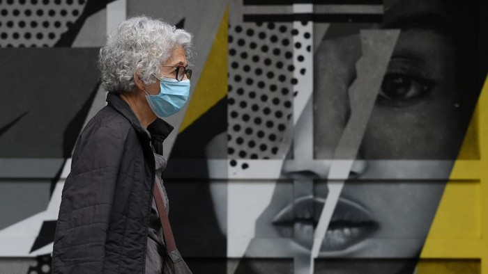 A woman wearing a face mask walks past a graffiti in Barcelona on October 21, 2020. - Spain has become one of the pandemics hotspots in the European Union, with close to 975,000 registered cases and nearly 34,000 deaths. (Photo by LLUIS GENE / AFP)