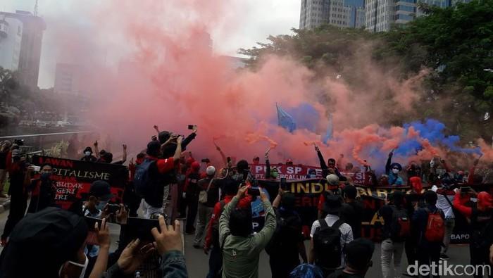Massa buruh nyalakan smoke bomb di Patung Kuda, Jakarta Pusat
