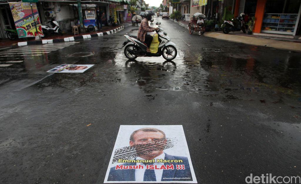 Pengendara melintas di atas poster berwajah presiden Prancis Emmanuel Macron yang ditempel di simpang Jalan Kauman, Yogyakarta, Rabu (28/10/2020). Pemasangan poster bergambar wajah Presiden Prancis tersebut sebagai bentuk protes dan kecaman terhadap pernyataan yang dilontarkan oleh Emmanuel Macron yang dianggap menghina umat muslim.