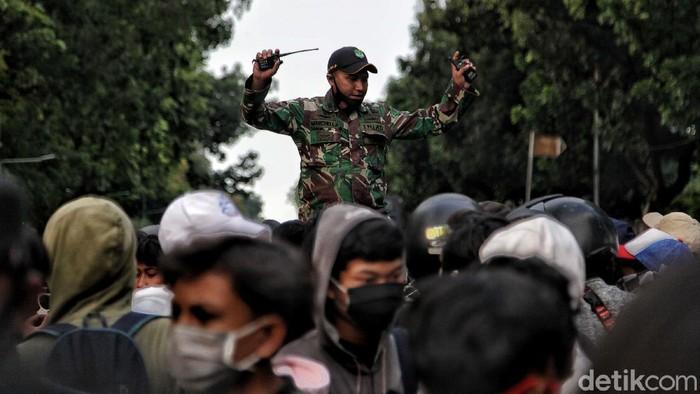Prajurit TNI mengawal massa remaja membubarkan diri dari kawasan Patung Kuda, Jakarta Pusat, Rabu (28/10/2020). Sebelumnya massa remaja itu sempat menggelar aksi bakar ban bekas.