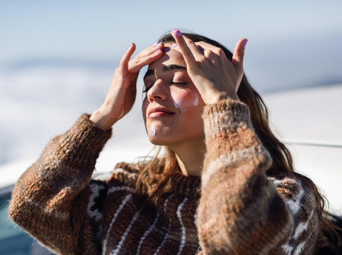 Young woman applying sunscreen on her face in snowy mountains in winter, in Sierra Nevada, Granada, Spain. Female wearing winter clothes.