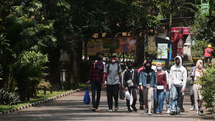 Pengunjung berposse di kandang Gajah sumatera saat mengisi waktu libur di Taman Margasatwa Ragunan, Jakarta