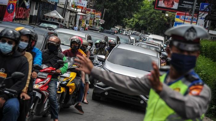Anggota kepolisian mengalihkan jalur menuju kawasan wisata Lembang di Jalan Setiabudi, Bandung, Jawa Barat, Kamis (29/10/2020). Pada cuti bersama serta libur panjang Maulid Nabi Muhammad SAW hari kedua, jalur wisata menuju Lembang dipadati kendaraan wisatawan, dan kepolisian memberlakukan pengalihan arus untuk mengurai kemacetan. ANTARA FOTO/Raisan Al Farisi/aww.