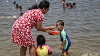 Anak-anak tersebut tampak bermain air dan pasir serta berenang di Pantai Ancol.