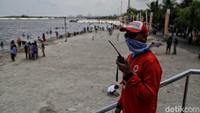 Seorang petugas mengawasi area Pantai Ancol.